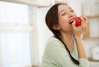 りんごをかじる女性